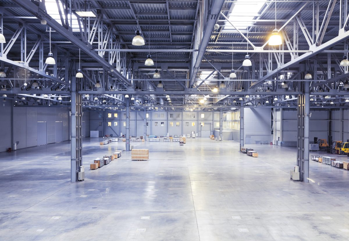 empty room of modern storehouse with forklift truck loader on a foreground. Top view.